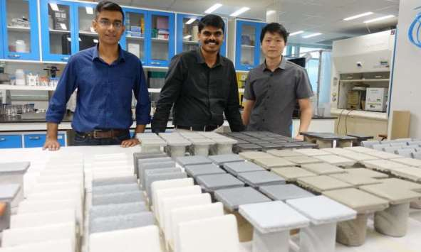 NTU scientists stand behind rows of coated steel plates used in their research and development efforts. Photo courtesy of NTU Singapore.