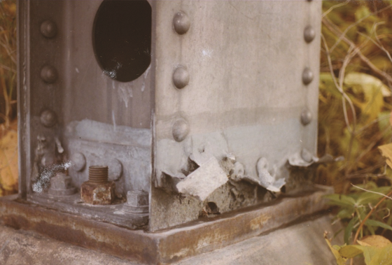 FIGURE 2 Base of an aluminum column showing exfoliation corrosion and partially blocked, semi-circular drainage holes.