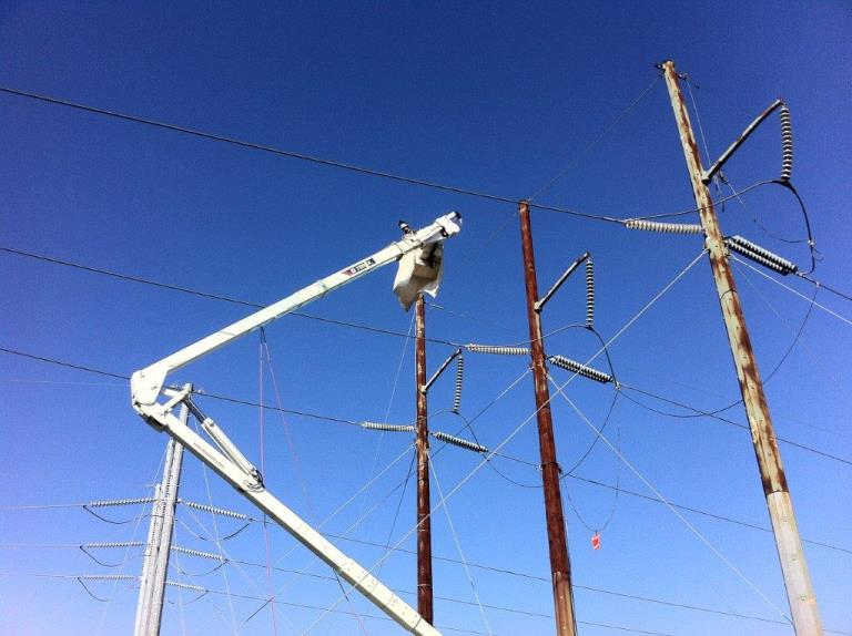 Workers perform surface preparation on a de-energized 138-kV pole prior to the application of an epoxy coating system. Photo courtesy of Cris Conner.